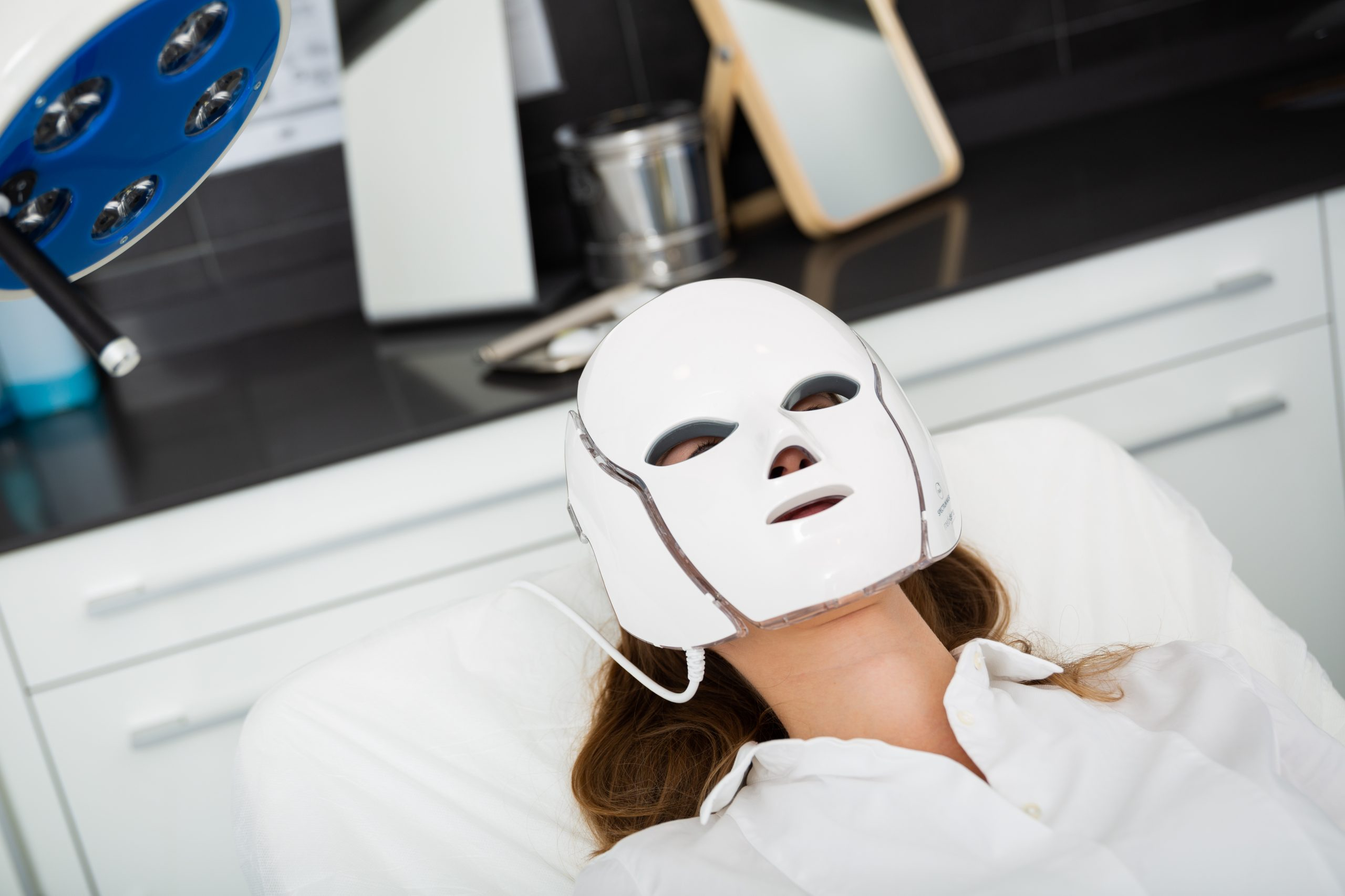 Female client getting face skin phototherapy procedure on modern professional equipment in clinic of aesthetic cosmetology.