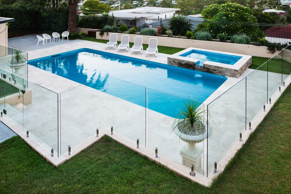 Modern,Swimming,Pool,Covered,With,Glass,Panels,Beside,A,Green